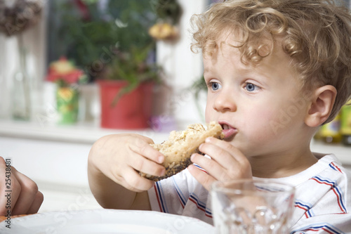 germany, berlin, boy (3-4) holding bread roll, portrait, close-up