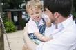Deutschland, Vater und Sohn Kleinkind am Spielplatz, lachen, Portrait, close-up