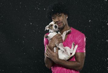 Mann trägt seinen Hund im Regen