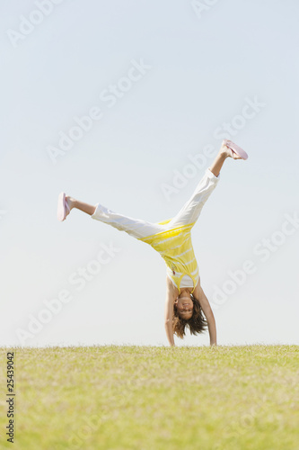 spain, mallorca, girl (10-11) doing  cartwheel in meadow
