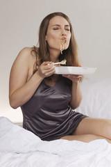 Frau sitzt auf dem Bett und isst asiatisches Essen