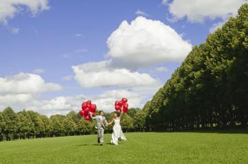 Deutschland, Bayern, Braut und Bräutigam, die rote Luftballons, im Freien