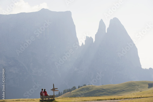 italy, south tyrol, seiseralm, couple sitting on bench, rear view