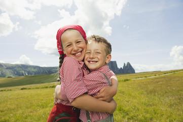 Italien, Seiseralm, Junge und Mädchen im Feld, umarmen, lächeln, Porträt