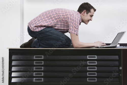 man kneeling on desk using laptop