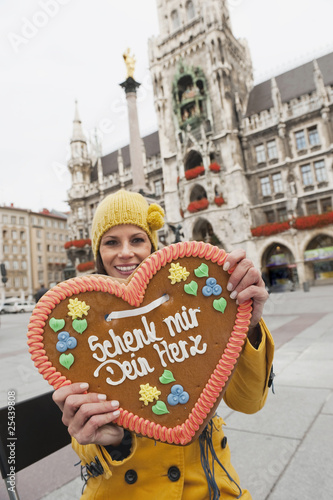 germany, bavaria, munich, marienplatz, woman holding gingerbread heart, smiling, portrait