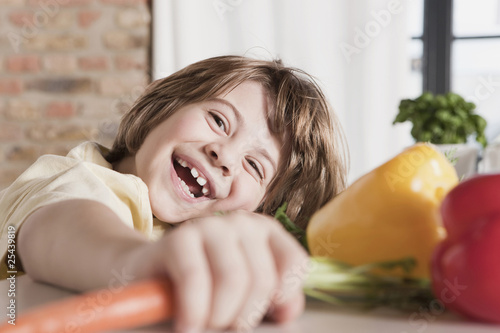 germany, cologne, boy (6-7) in kitchen holding carrot, laughing, portrait, close-up