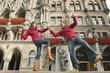 Deutschland, Bayern, München, Marienplatz, Paar balancieren auf Brunnen, das Bier halten Becher, lächeln, Porträt