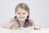 girl (4-5) counting stack of coins, smiling, portrait