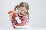 girl (4-5) pouring ketchup on spagetti