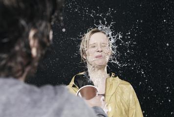 Ein Mann bespritzt eine Frau mit Wasser