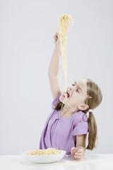 Mädchen essen Spagetti, die Augen geschlossen