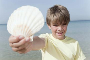 Spanien, Mallorca, Junge mit Muschel am Strand, Portrait