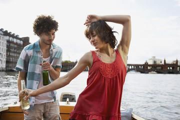 Deutschland, Berlin, Junges Paar auf dem Motorboot, Mann suchen Frau, Tanz, Portrait