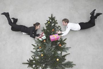 Geschäftsmann und Geschäftsfrau fliegen vor dem Weihnachtsbaum