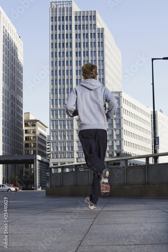 germany, berlin, young man jogging on street
