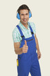 man wearing ear muff showing thumbs up sign, smiling, portrait
