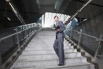 Deutschland, Bayern, München, Geschäftsfrau Frau mit Handy am U-Bahn-Station, stehen auf Treppe