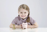 girl (4-5) holding piggy bank and stack of coins, smiling, portrait