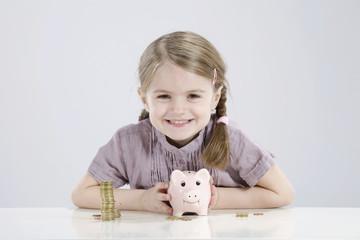 Mädchen halten Sparschwein und Stapel von Münzen, Lächeln, Portrait