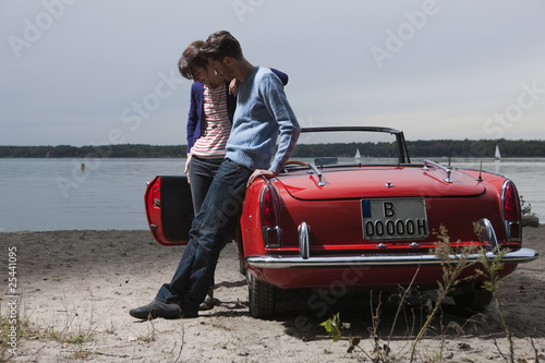 germany, berlin, lake wannsee, young couple standing by cabriolet, looking down