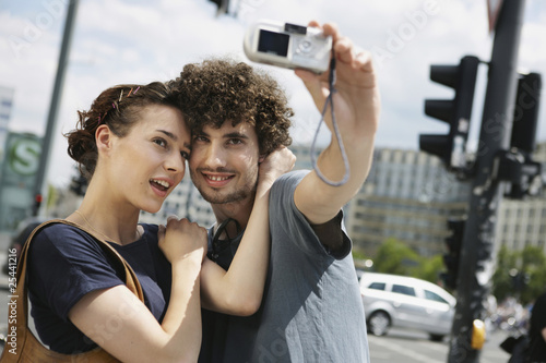 germany, berlin, young couple taking a photograph of themselves