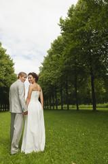 Deutschland, Bayern, Brautpaar im Park Hände halten, lächeln, Porträt