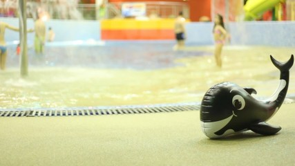 Inflatable whale is near pool, where children bathe