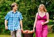 Paar trägt Korb mit Äpfeln