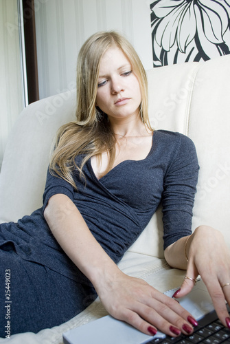 Pretty female teen using her notebook on the couch in her room