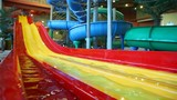 Large plastic slide is filled water in large indoor waterpark