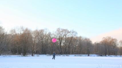 boy kicking big air-balloon in wintry snowfield