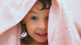cute happy little girl dries by towel in bathroom