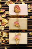 Row of soap and rose withered petals on bamboo mat poster