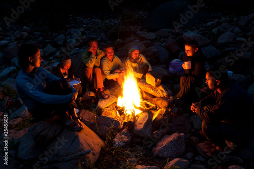 Tuinposter Kamperen People near campfire in forest.
