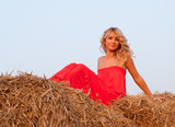 Beautiful blond young woman on a haystack