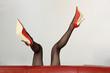 Sexy Frau in roten High-Heels liegt auf dem Sofa
