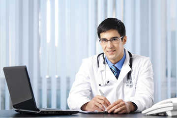 Successful doctor with laptop, at office