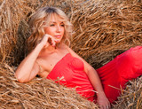 Beautiful blond young woman in a haystack