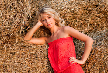 Beautiful blond young woman near haystack