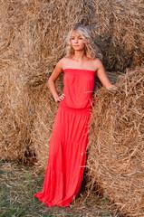 Beautiful blond woman near haystack
