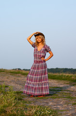 Beautiful blond young woman in a cowboy hat and dress