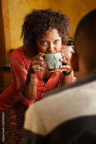 African-American woman talks with male in kitchen