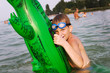 Young boy hold his green floater crocodile in the water