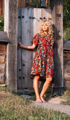 Beautiful blond young woman in the wooden gate