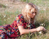 Beautiful blond young woman with wild flowers