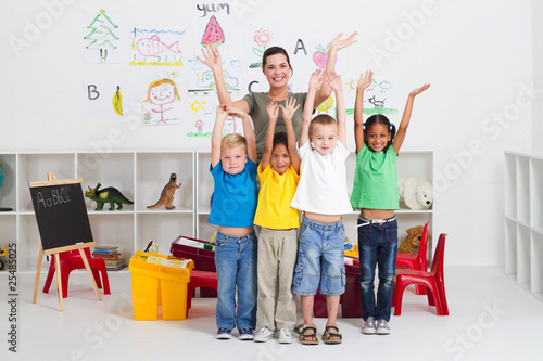 cheerful teacher and preschool kids in classroom