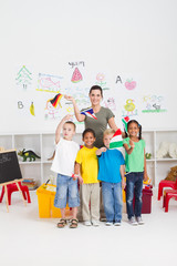 happy preschoolers and teaching waving flags in classroom