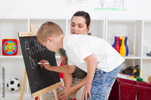 teacher helping young student write on chalkboard