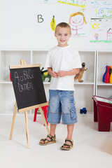 cute preschool boy writing on chalkboard